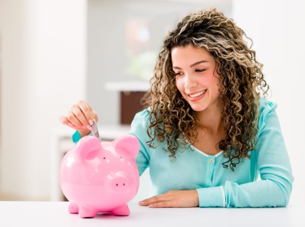 Woman depositing money piggy bank