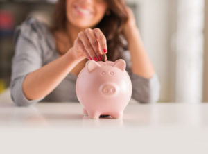 Woman putting Money Piggy Bank