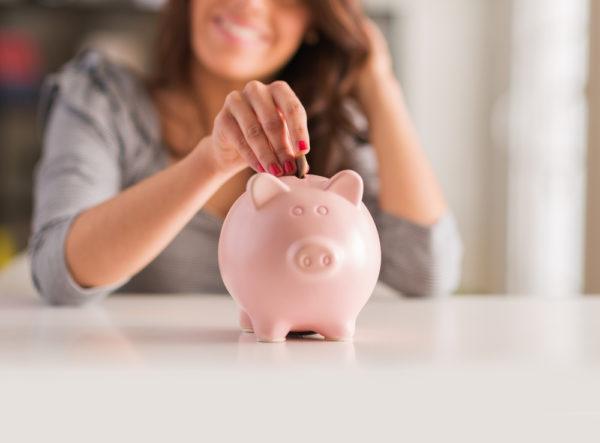 Woman putting Money Piggy Bank