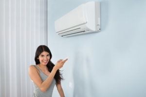 Woman Pointing to Air Conditioning