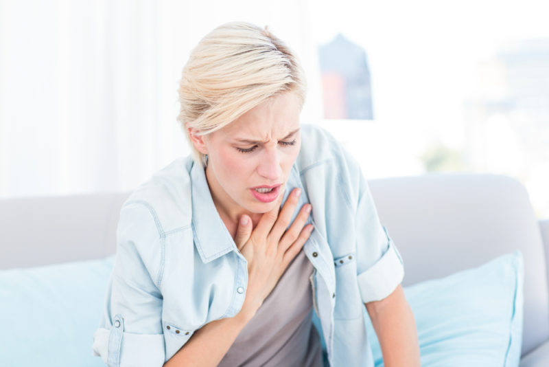 Woman Clutching chest Allergies
