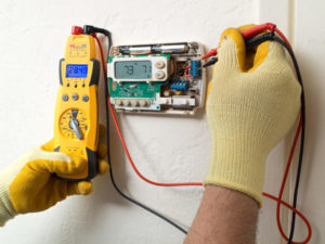 Man Checking Thermostat Equipment