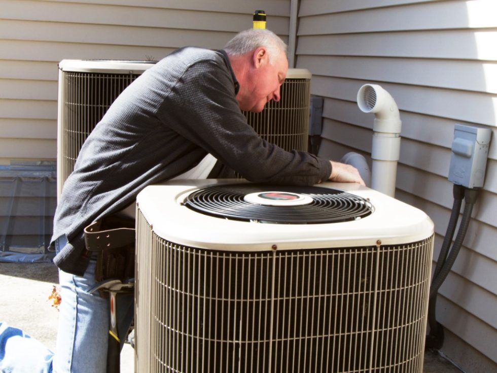 Man Inspecting Air Conditioner AC