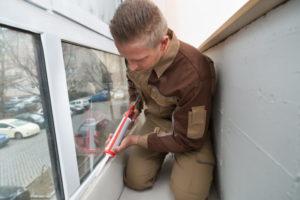 Man Sealing Window