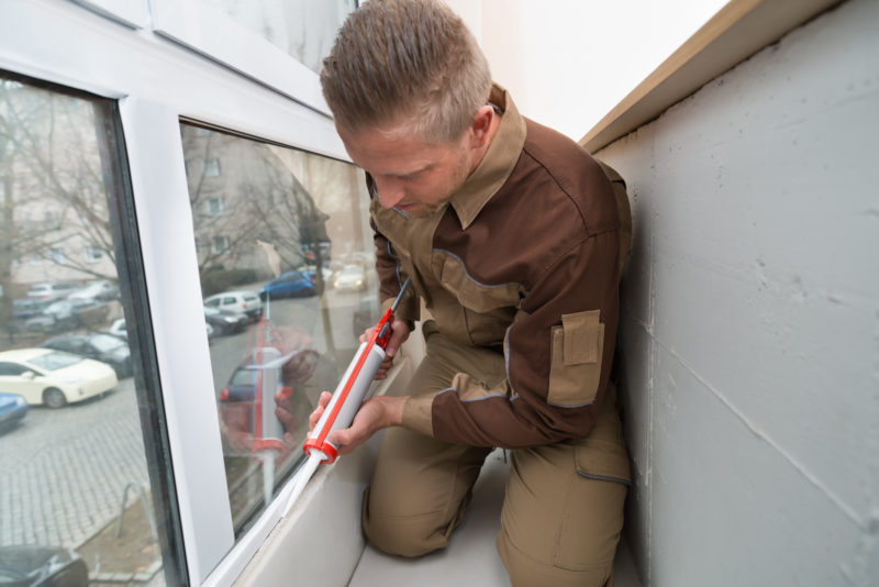 Man Sealing Window