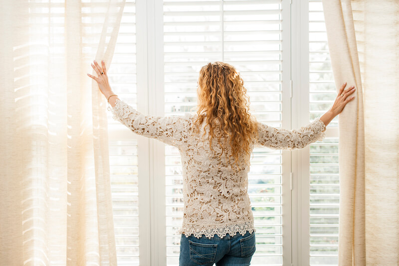 Woman Opening Blinds